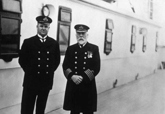 """Thuyền trưởng Edward J. Smith (bên phải) người tuyên bố rằng: """"Ngay cả ĐỨC CHÚA TRỜI cũng không thể đánh chìm con tàu này!"""" chụp trên boong tàu Titanic cùng đồng nghiệp, người quản lý Hugh Walter McElroy,"""